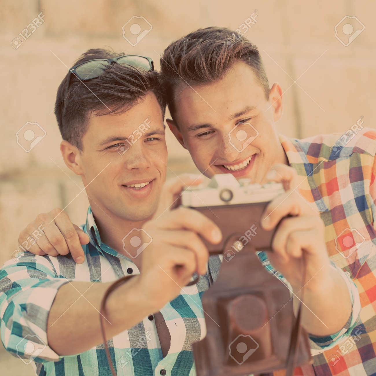 two guys photographing with retro photo camera stock photo picture