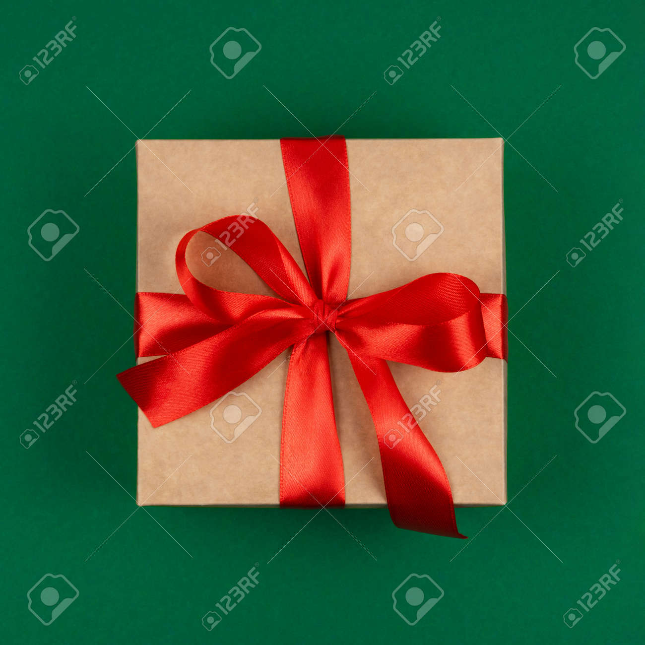 Top view of craft Merry Christmas gift with red bow ribbon over green background. Happy New Year greetings. Festive winter holidays backdrop. Flat lay. Happy Birthday card. - 158170698