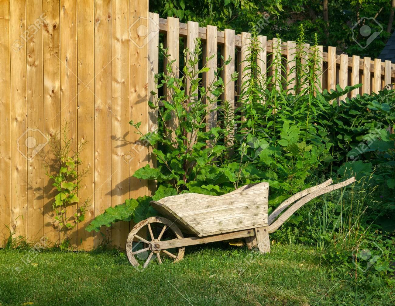 Decorative Wooden Wheelbarrow Planter Near Wooden Fence Stock Photo ...