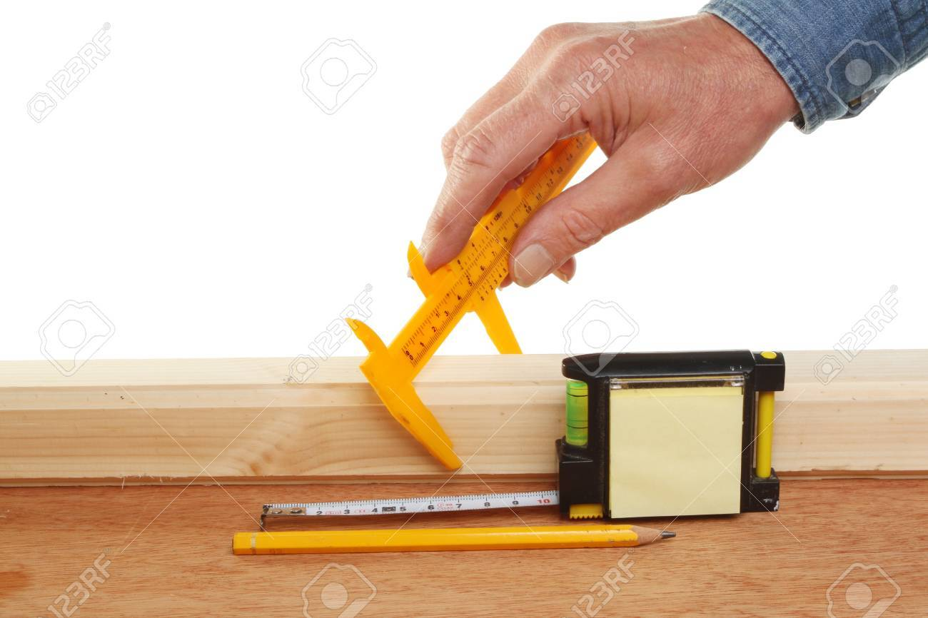 Hand measuring wood with a guage and tape measure Stock Photo - 14771302