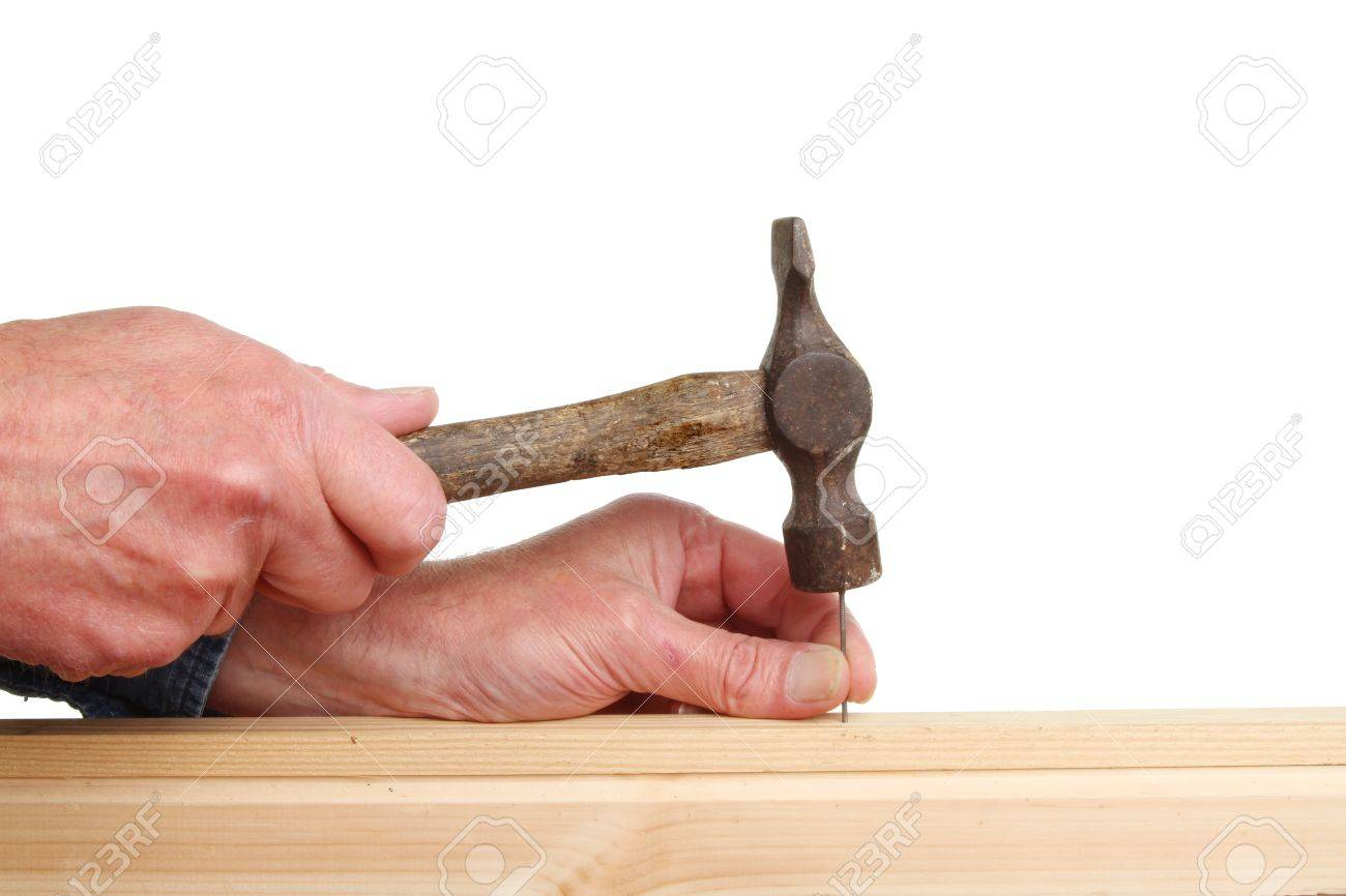 Hands nailing two pieces of wood with an old tack hammer Stock Photo - 14771301