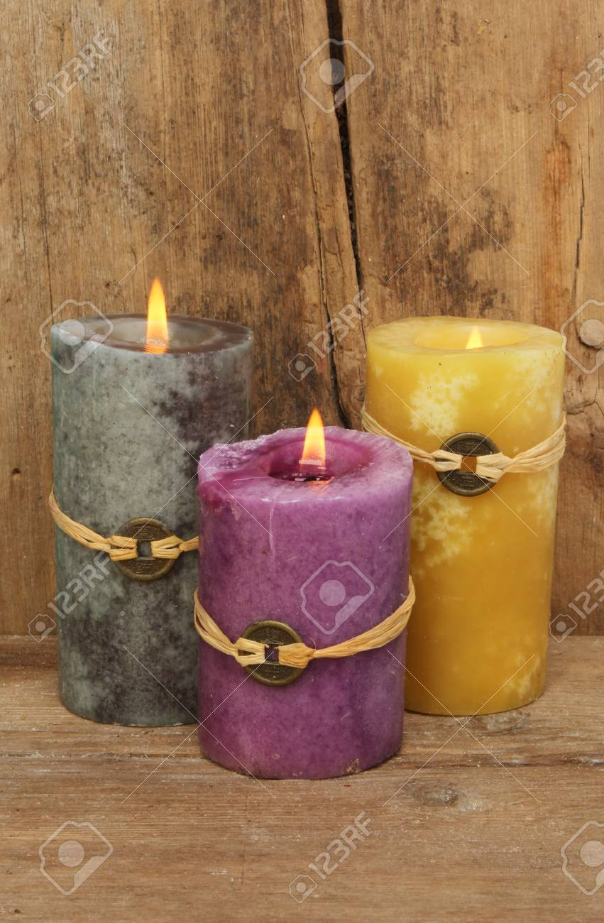 Feng Shui Kaarsen.Three Feng Shui Candles Against A Background Of Old Weathered