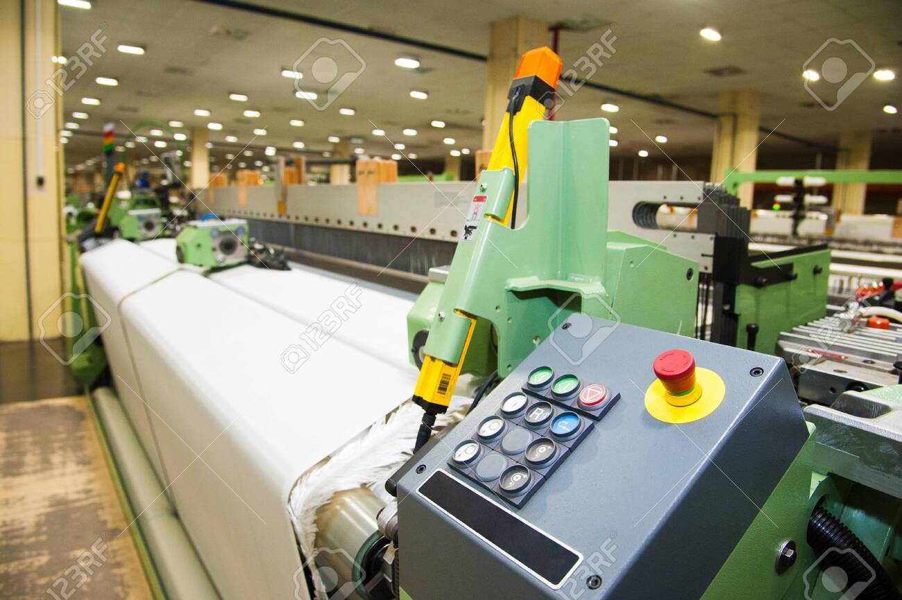 Industrial fabric production line. Weaving looms at a textile factory - 131076082