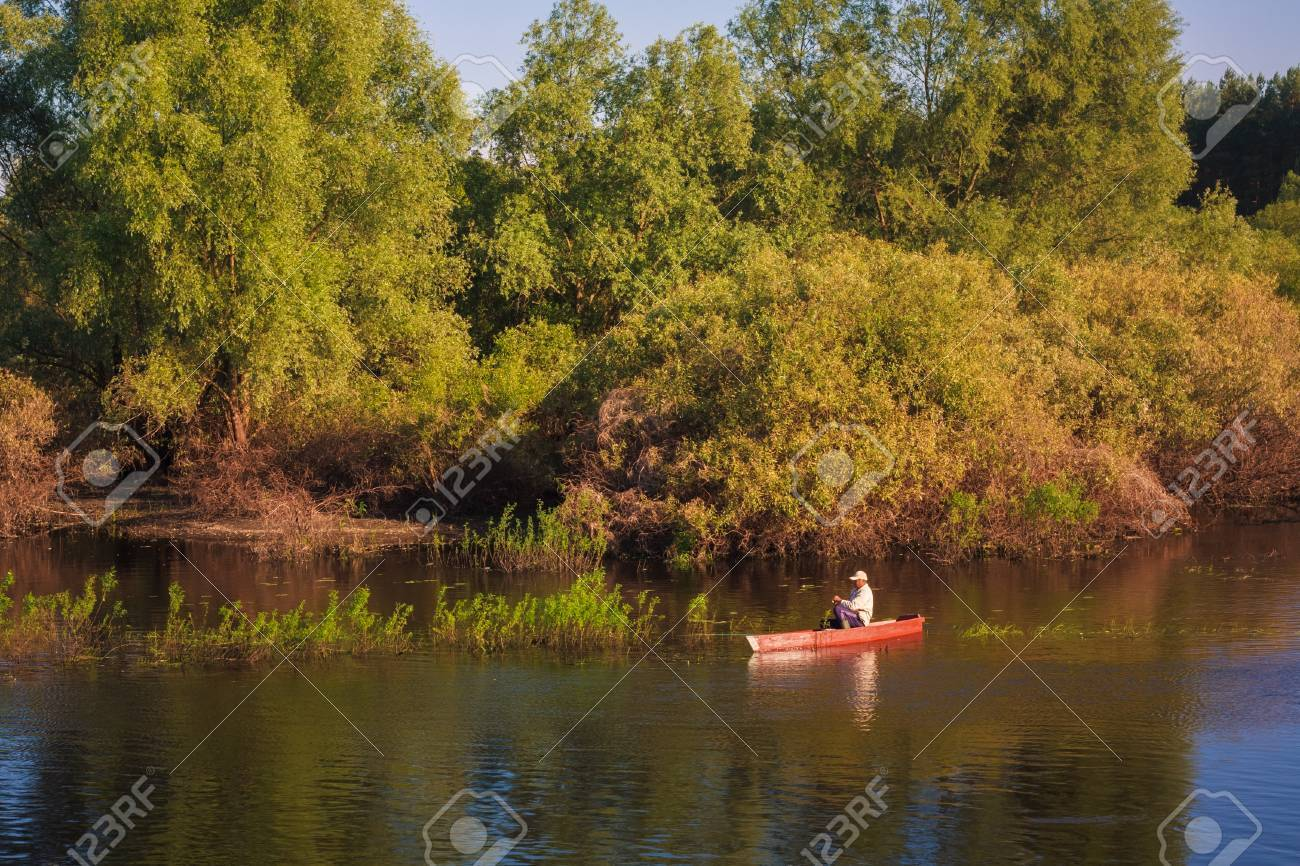 Old man fishing out of a row boat Stock Photo - 21520630