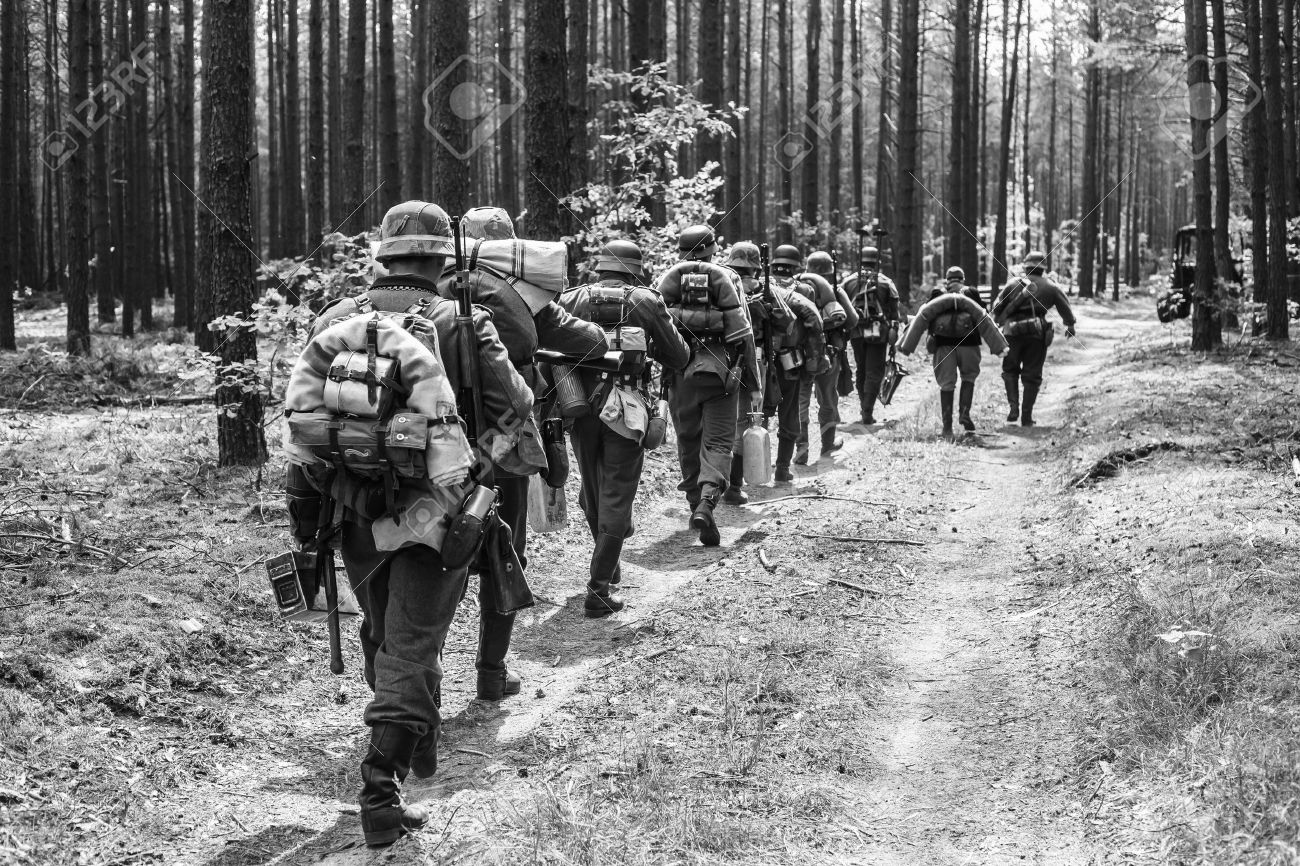 Stock photo unidentified re enactors dressed as world war ii german soldiers walks on forest road black and white photography