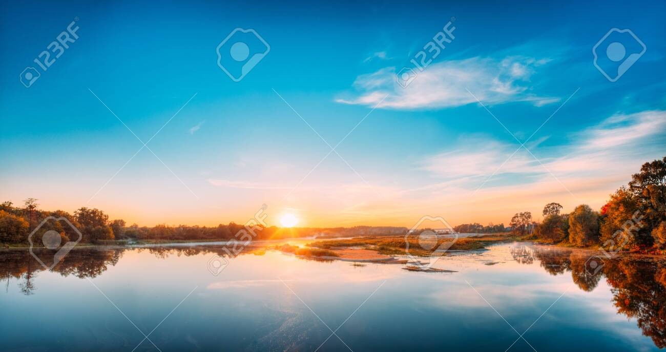 Autumn River Landscape In Belarus Or European Part Of Russia At Sunset. Sun Shine Over Blue Water Lake Or River At Sunrise. Nature At Sunny Morning. Woods With Orange Foliage On Riverside - 148701482