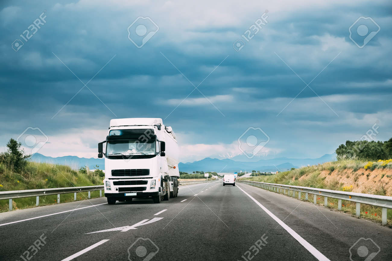 White Truck Or Traction Unit In Motion On Road, Freeway. Asphalt Motorway Highway Against Background Of Mountains Landscape. Business Transportation And Trucking Industry. - 149456716