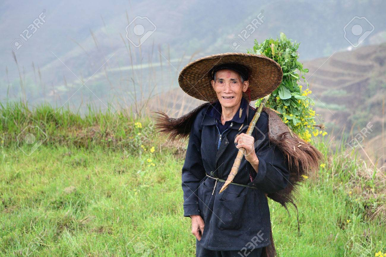 Yao Village Dazhai, Longsheng, Guangxi Province, China - April 3, 2010: Unknown Asian farmer in traditional Chinese hat, among the rice terraces. One person, the image of a horizontal orientation, for editorial use only. Stock Photo - 25386138
