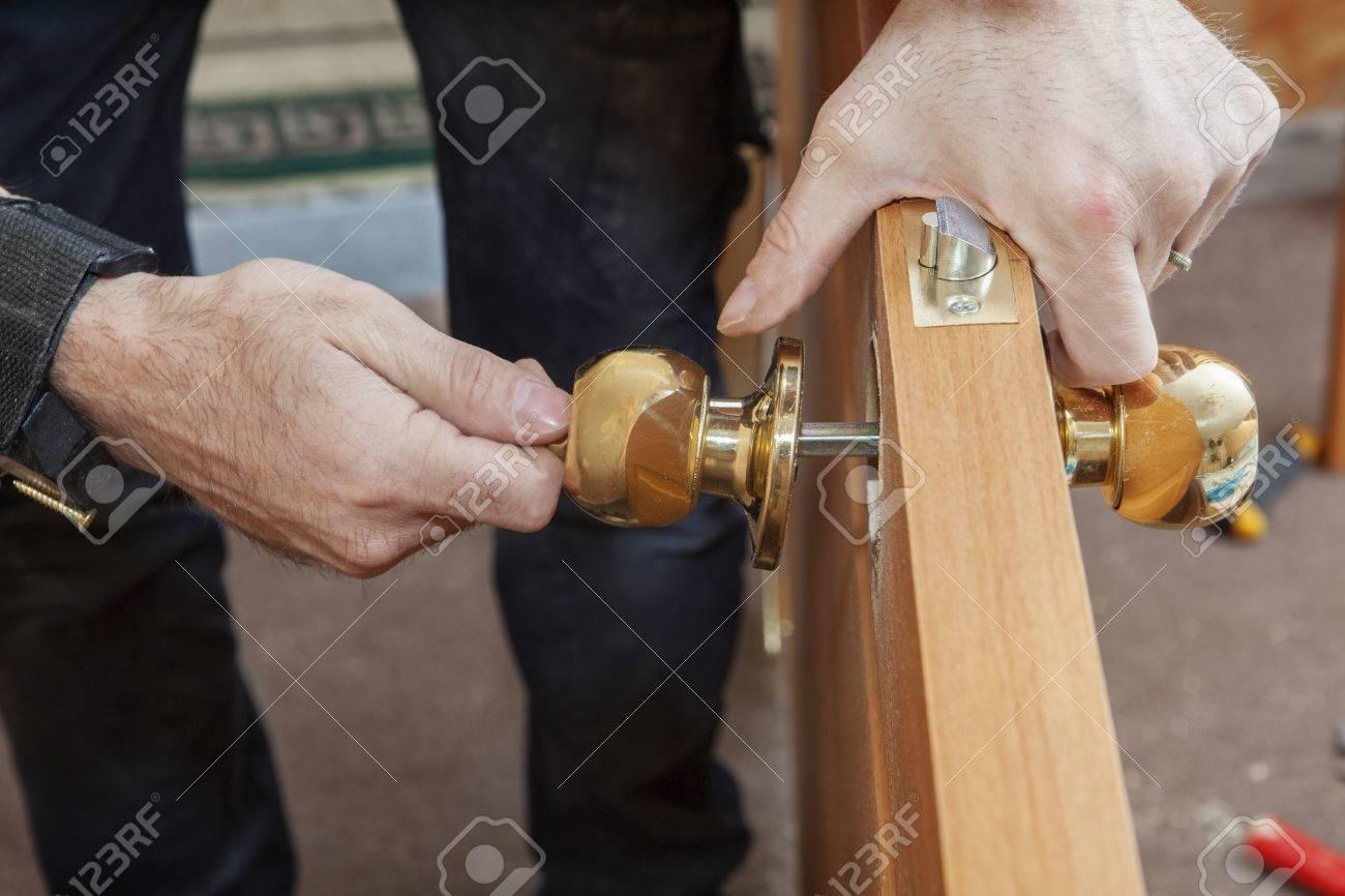 Carpenter Change door, Installing new door knob with lock, close-up human hend hold door handle. - 57978085