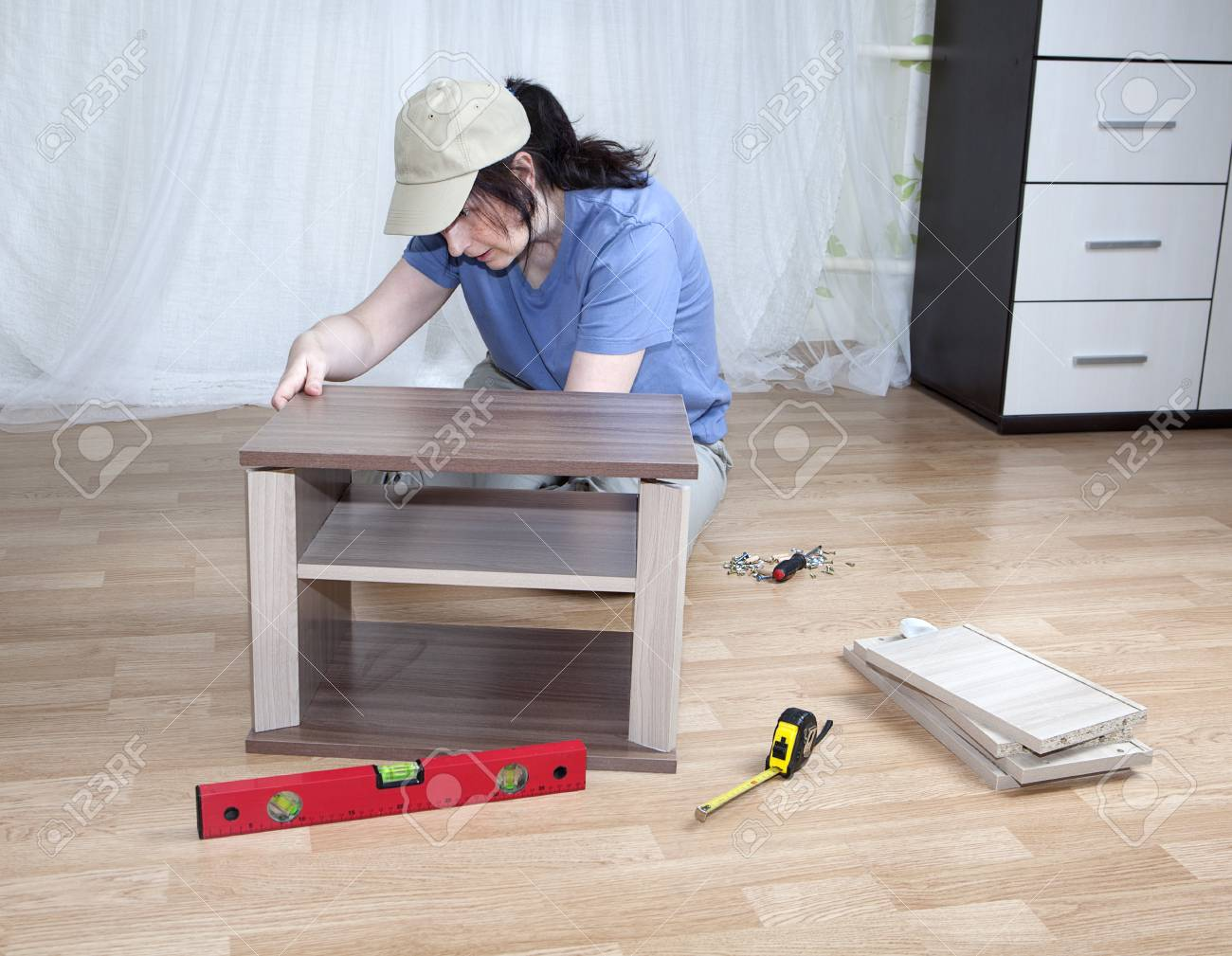 One Caucasian Woman Putting Together Self Assembly Furniture While Sitting  On Floor. Stock Photo