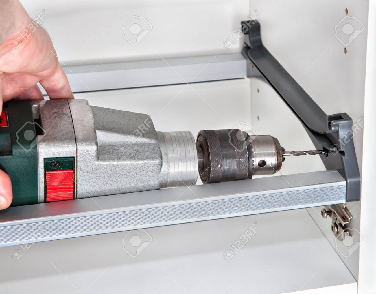 Instalación de muebles de cocina, montaje montaje de la pared del gabinete  para secar platos, el agujero carpintero se perfora utilizando taladro ...