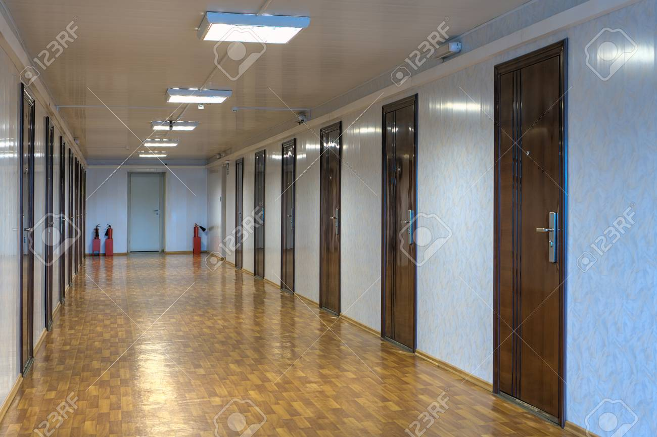 Long couloir de bureau avec de nombreuses portes en bois rouge foncé