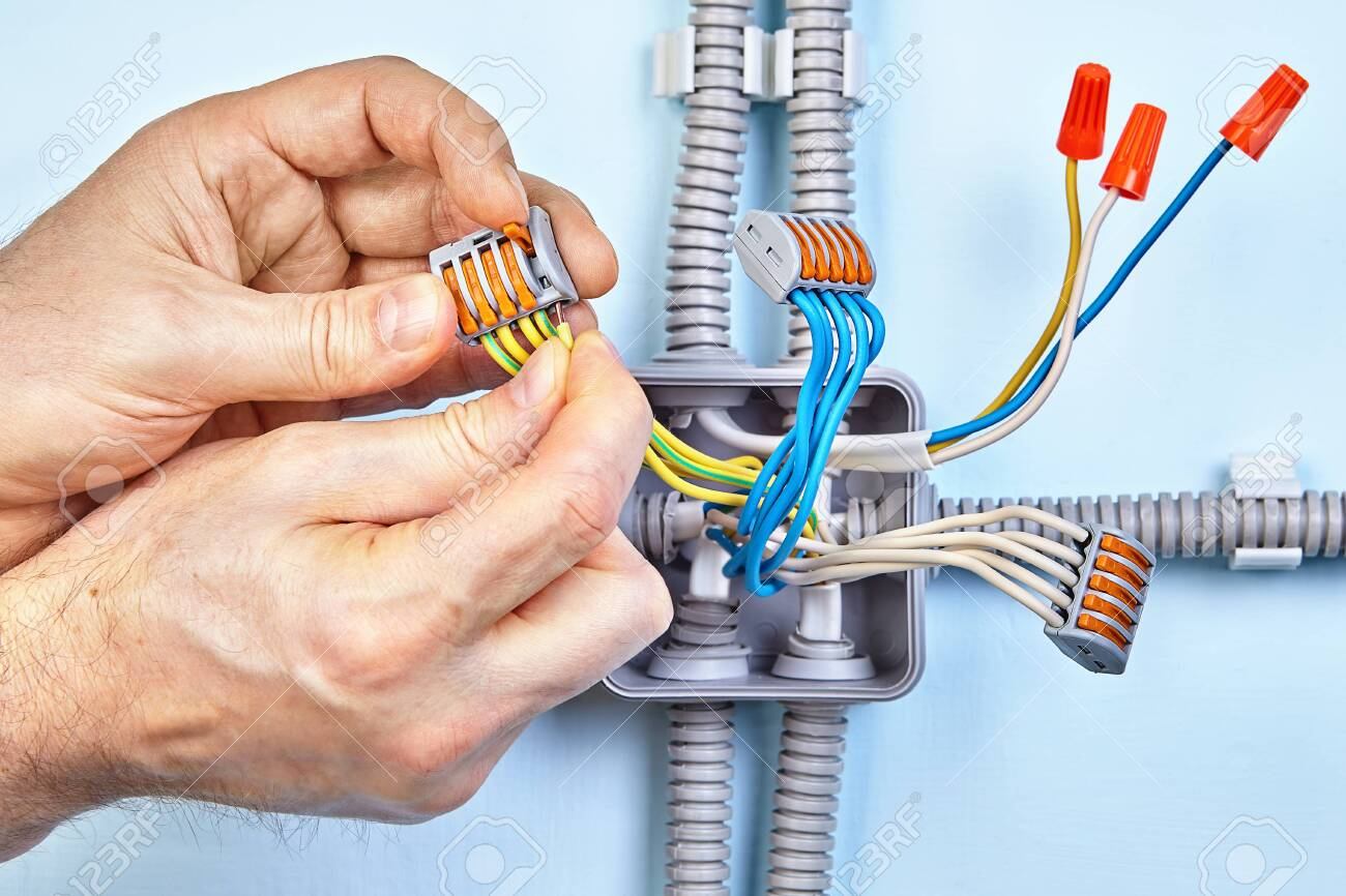 Electrician is making new junction box for electrical wires with.. on