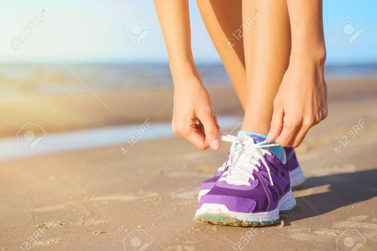 Woman wearing running shoes on the beach - 31675556