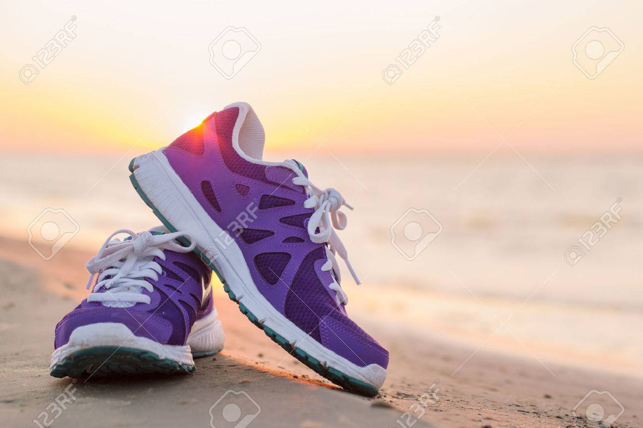Pair of running shoes on the beach at sunset Stock Photo - 32155280 bd7dc309a