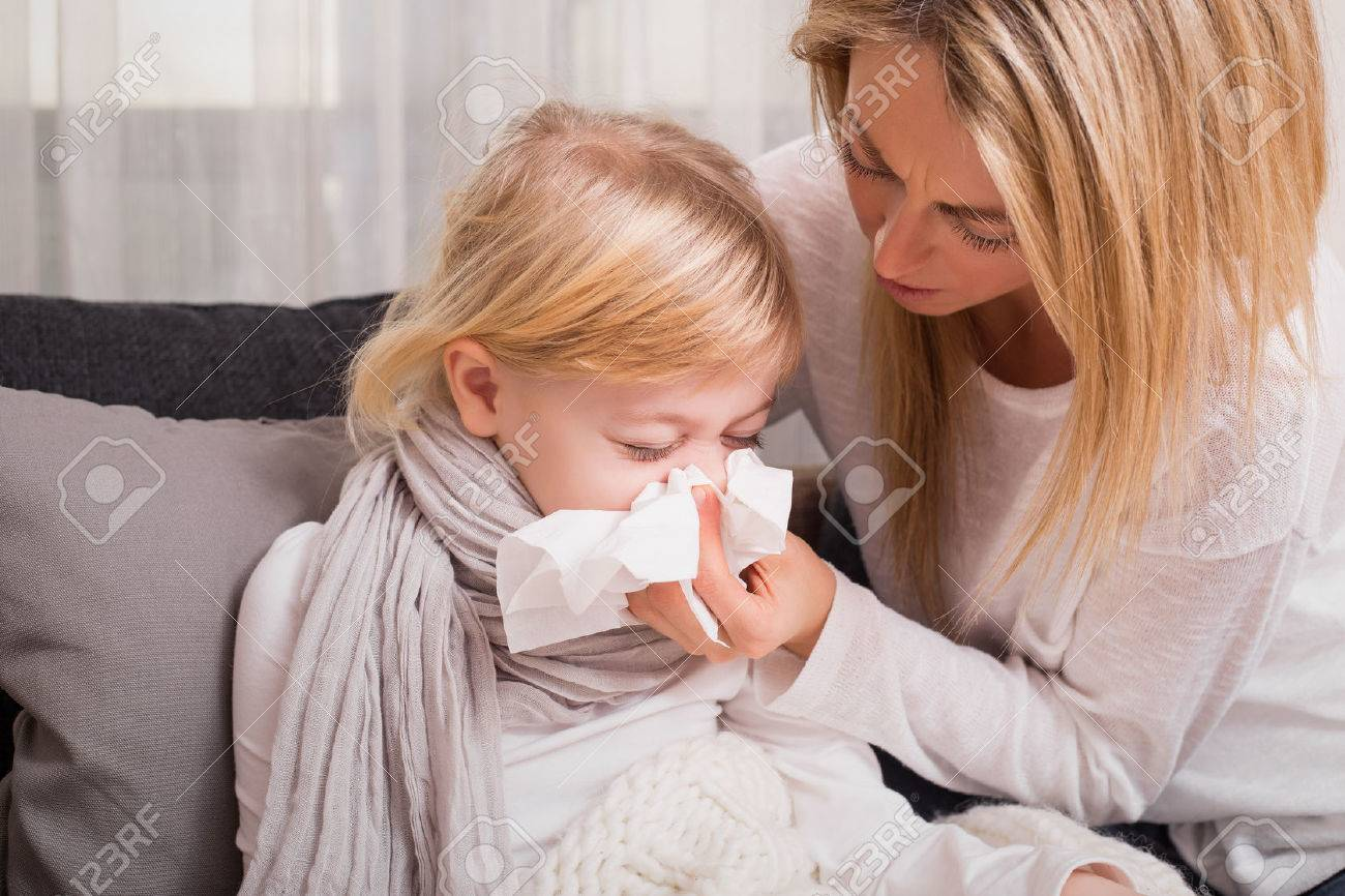 Little girl with cold and blowing her nose - 51904369