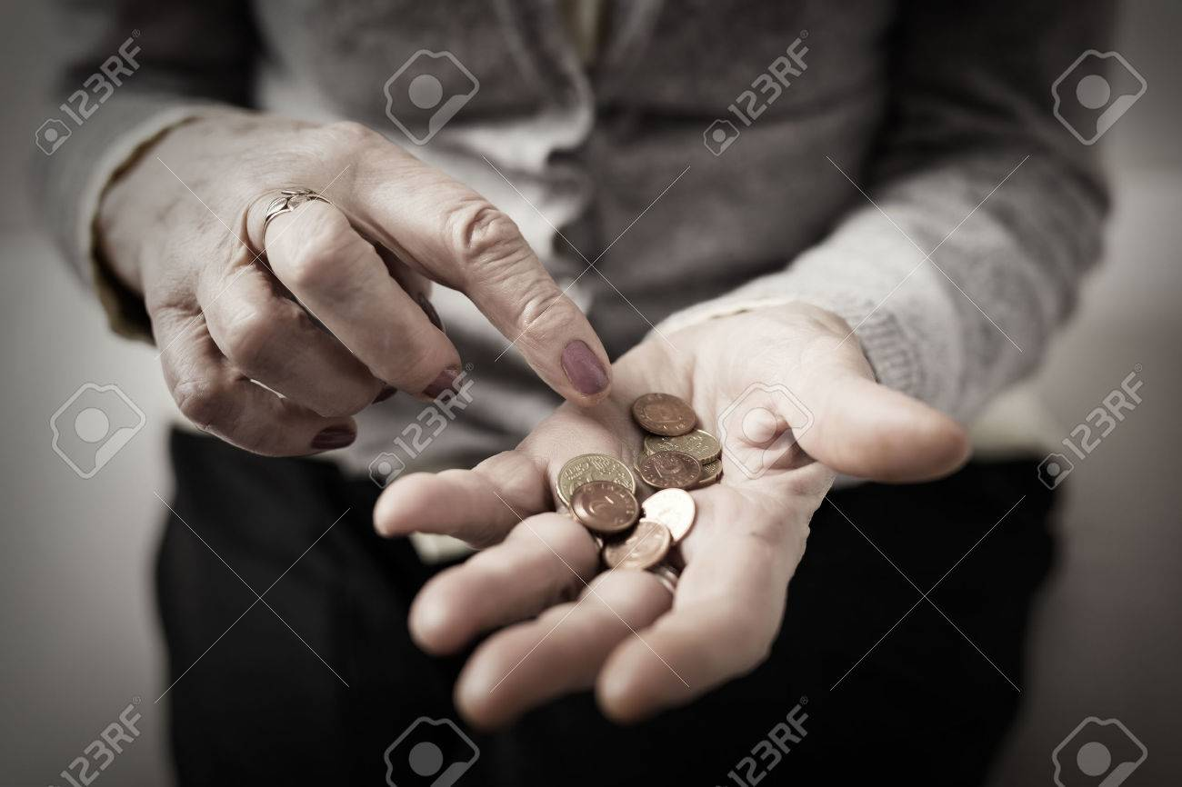 Older person counting money in her palm - 72222257