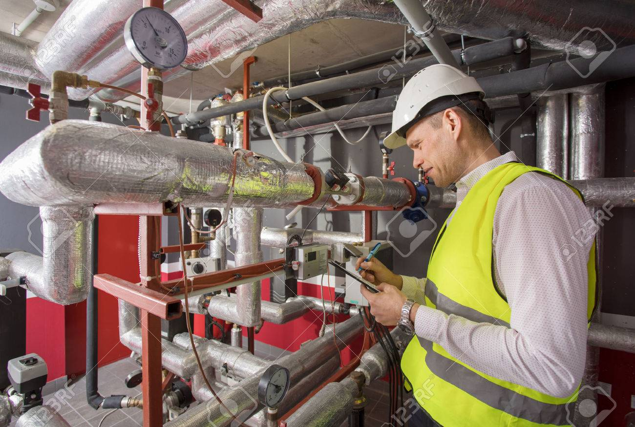 Man in helmet writing down measurements in heat and airconditioning system panel - 75727088
