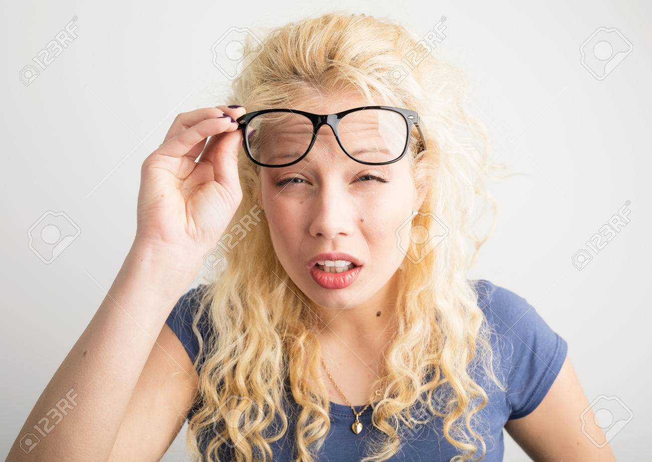 Woman with her glasses lifted up can't see - 75684630