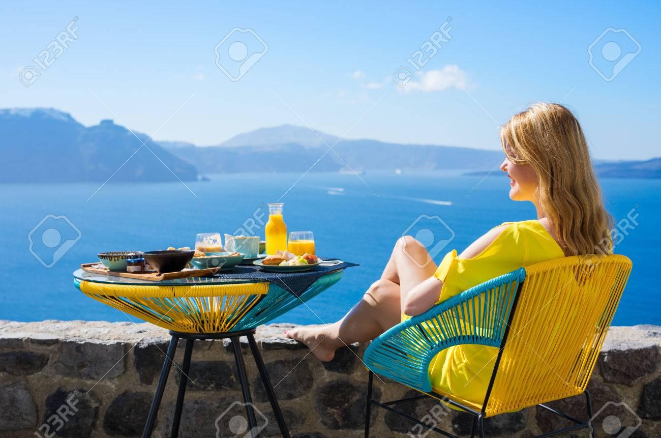 Woman enjoying luxurious breakfast with beautiful view from terrace - 80620386