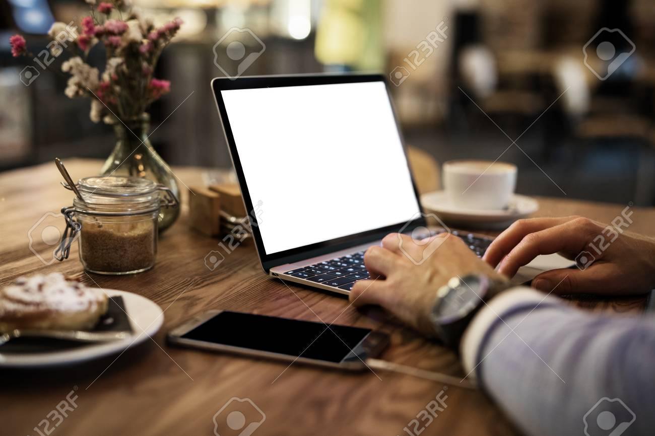Man using laptop in cafe - 91310094