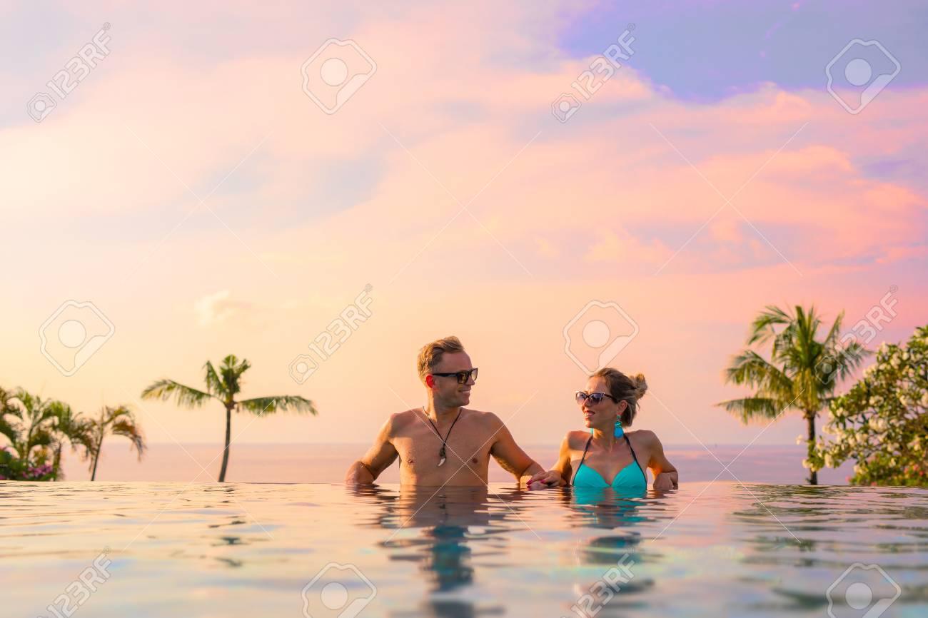 Couple relaxing in infinity pool of exotic luxury resort - 91381779