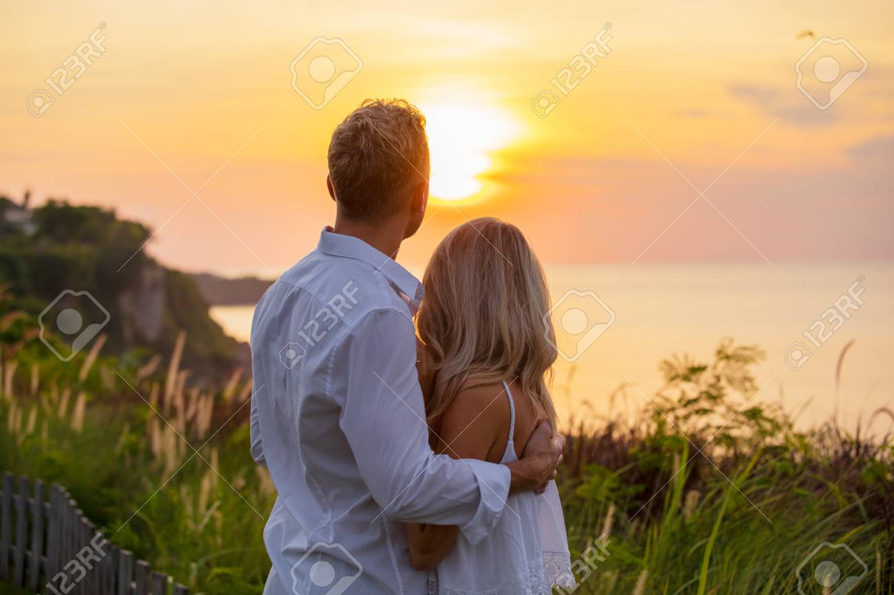 Romantic couple looking at sunset - 99618240