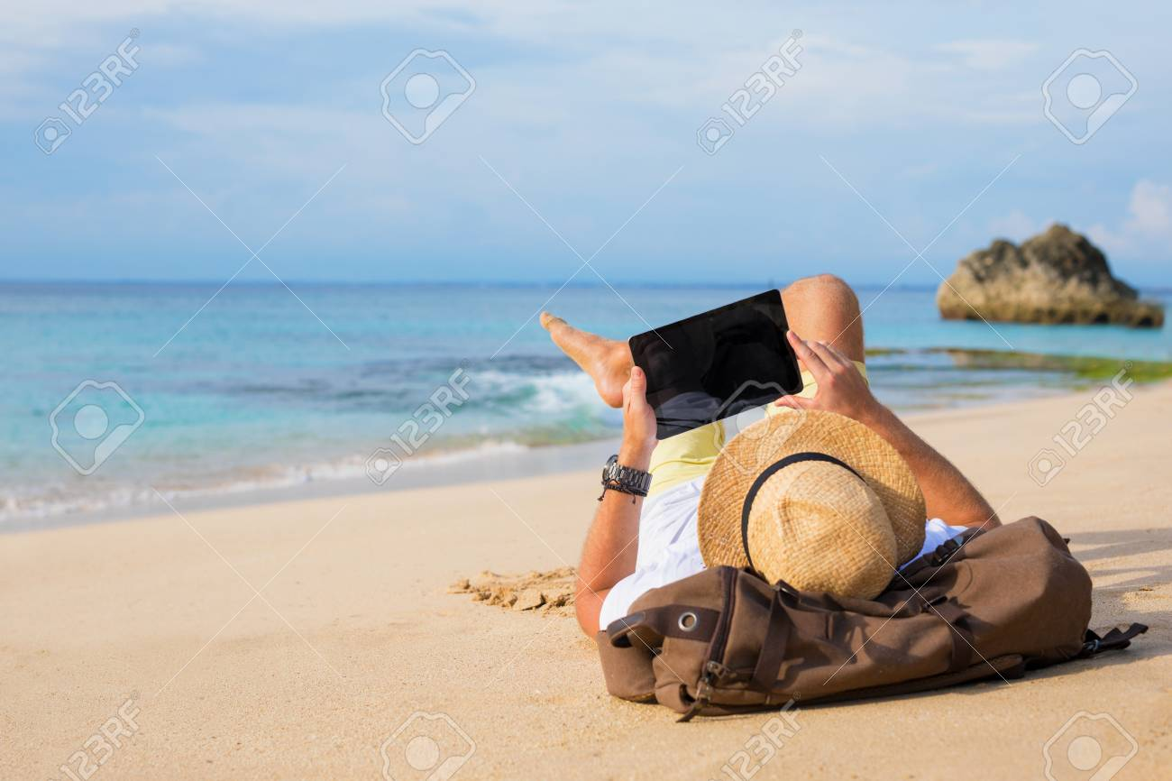 Man lying on the beach and using tablet - 99564114