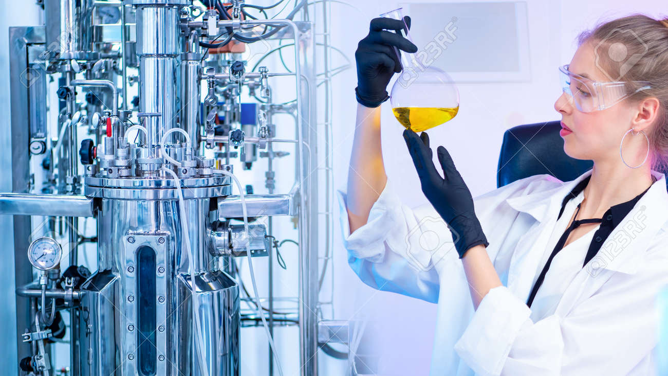 The girl looks at the yellow chemical liquid in the flask. Development of new vaccines. Bioreactor in the chemical laboratory. Research in the field of Microbiology. - 158409637