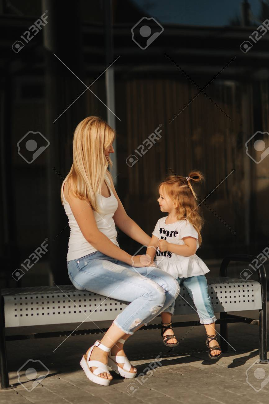 Mother and daughter outdoors in city  playing and having fun