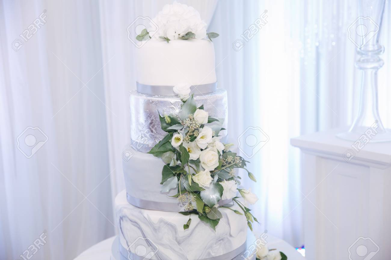 Beautiful Wedding Cake Decorated With Flowers Silver And White Color