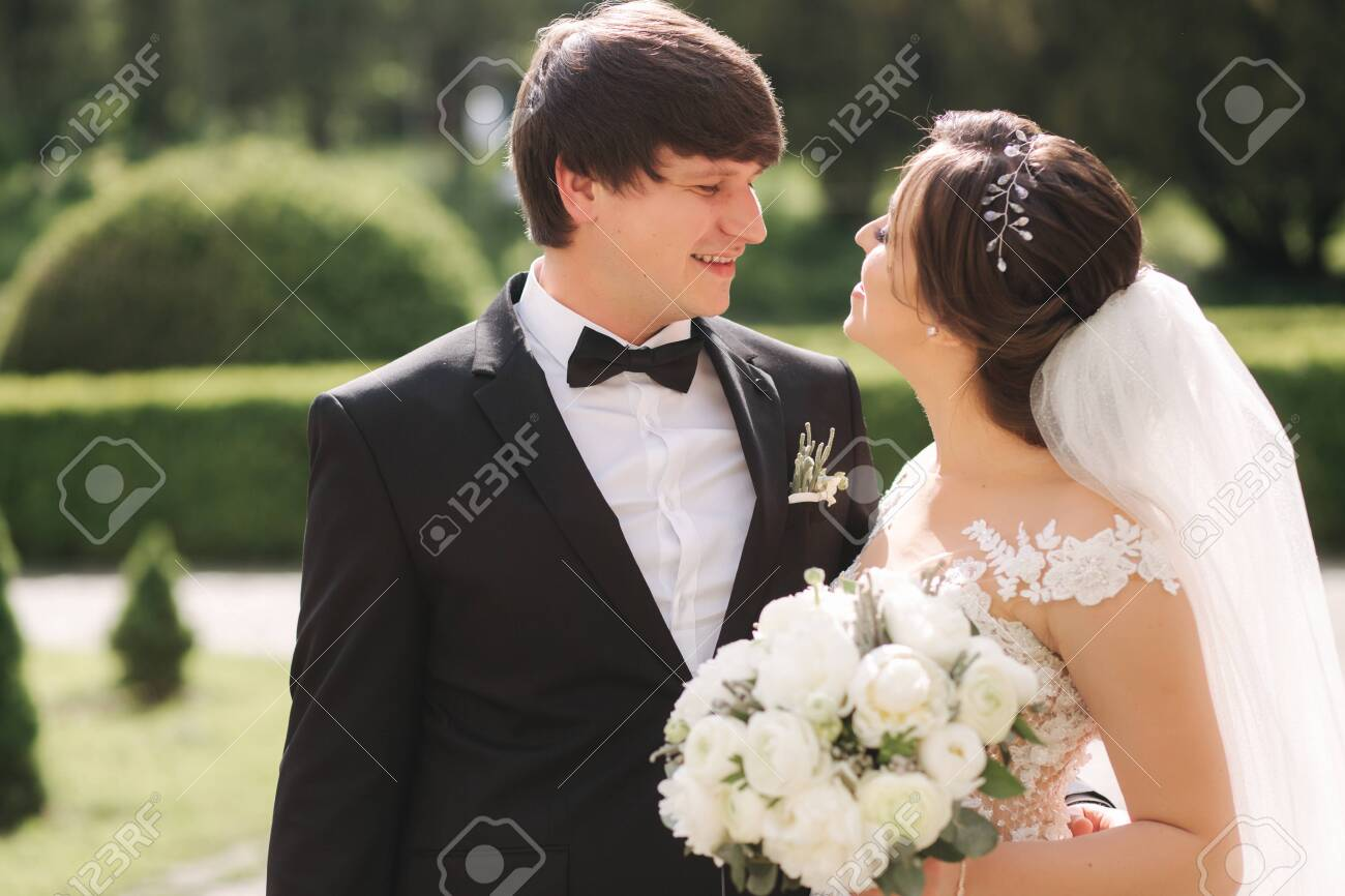 Close-up portrait of beautiful wedding couple. Handsome groom with gorgeous bride - 137838453