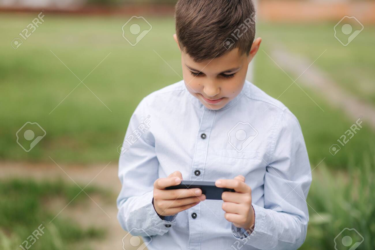 Young Boy Sitting On The Bench And Play Online Games During Quarantine Stock Photo Picture And Royalty Free Image Image 143704953