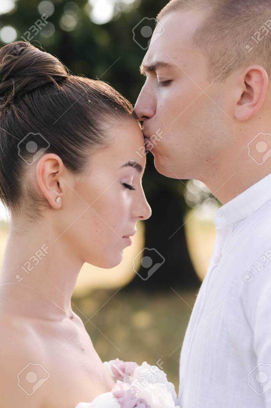 Close up portrait of groom kiss bride in forehead in front of big tree. Side view - 151996692