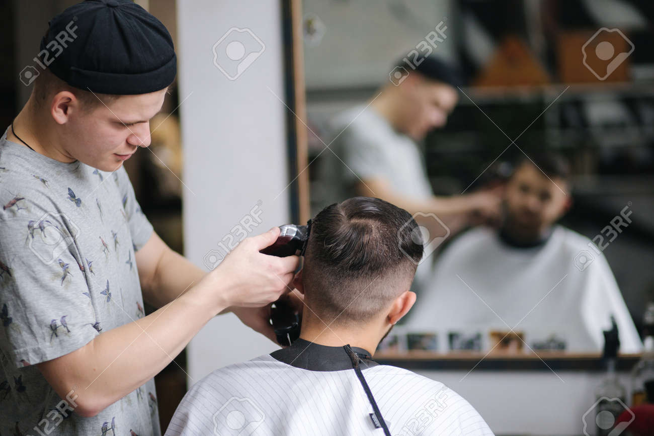 Handsome man getting haircut by barber while sitting in chair at barbershop. - 159138901
