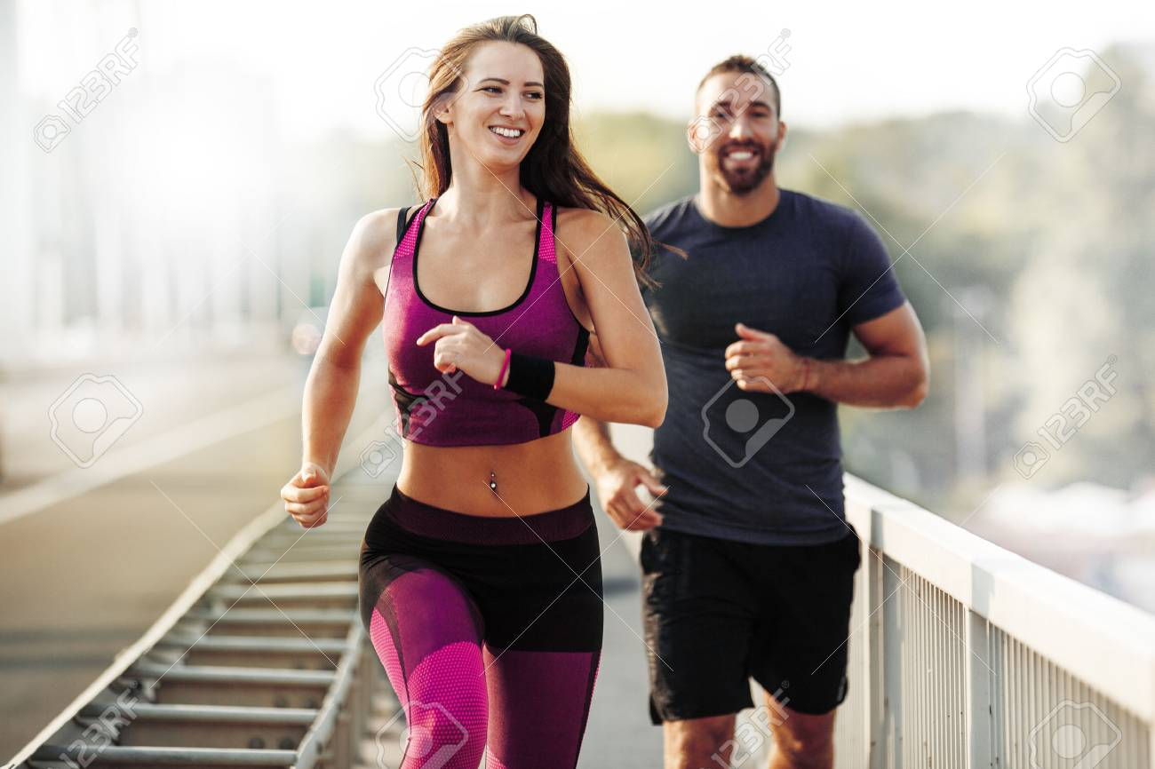 Happy couple running outdoors. People jogging together, living healthy lifestyle. - 62396849