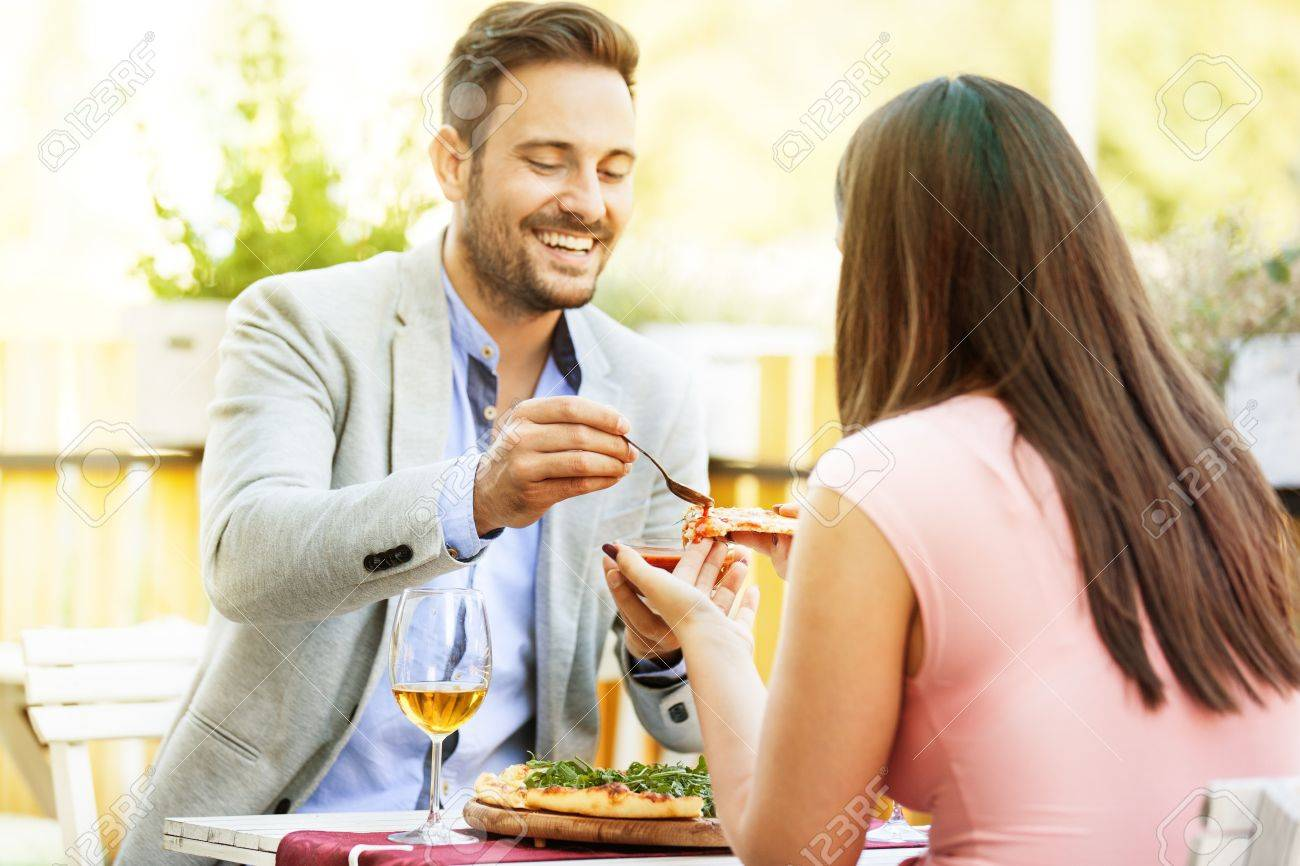Happy couple eating pizza in a restaurant. Selective focus on pizza. - 65159963