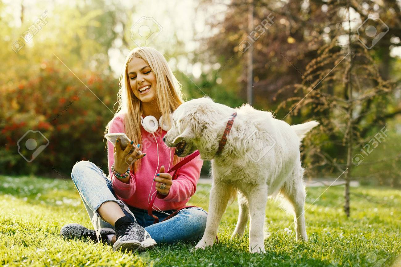 Young blonde woman is relaxing in the park with her retriever. - 84633093