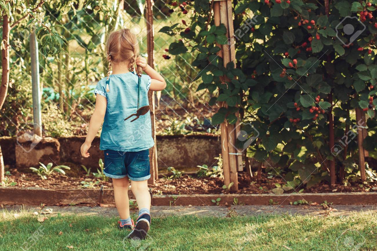Young Girl Is Ready For Hoeing Garden With Small Hoe. Stock Photo ...