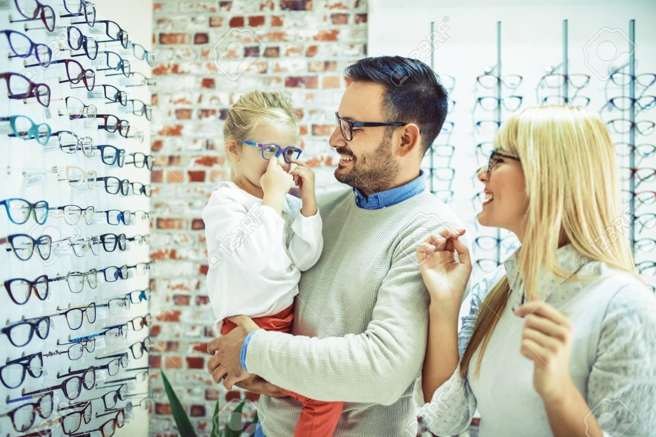 Happy family choosing glasses in optics store. - 87755456