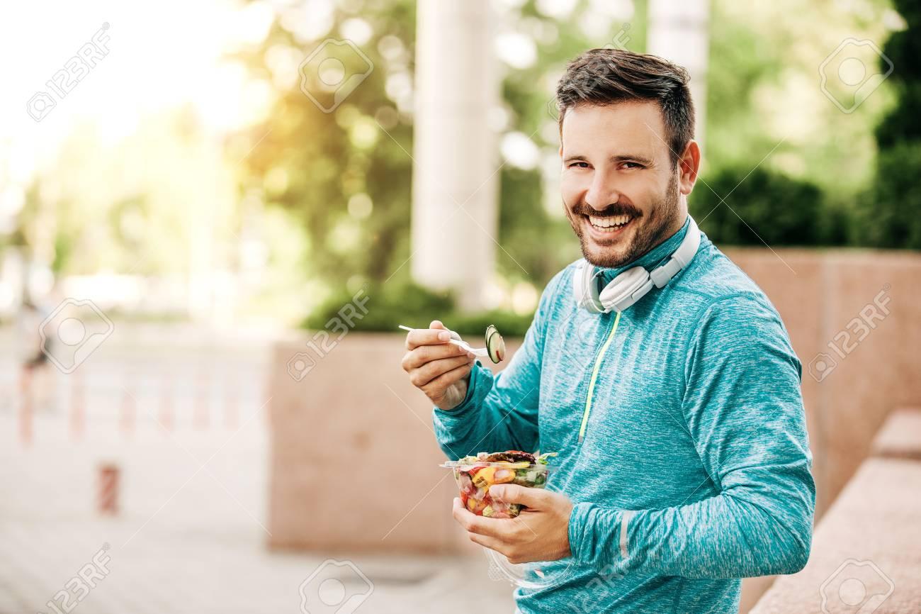 Young handsome man is enjoying vegetable salad after jogging. - 89678635