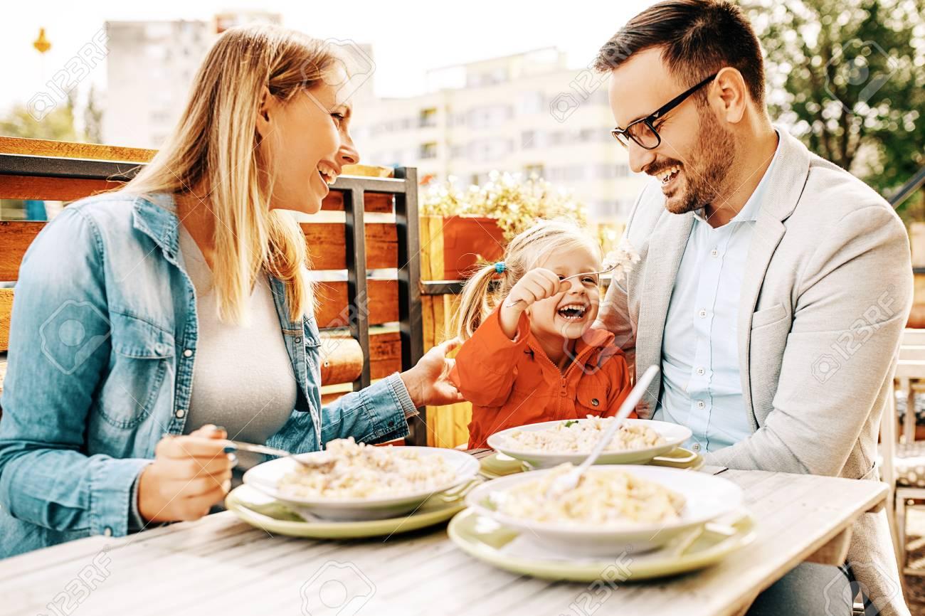Happy family is enjoying pasta in restaurant. - 89049169