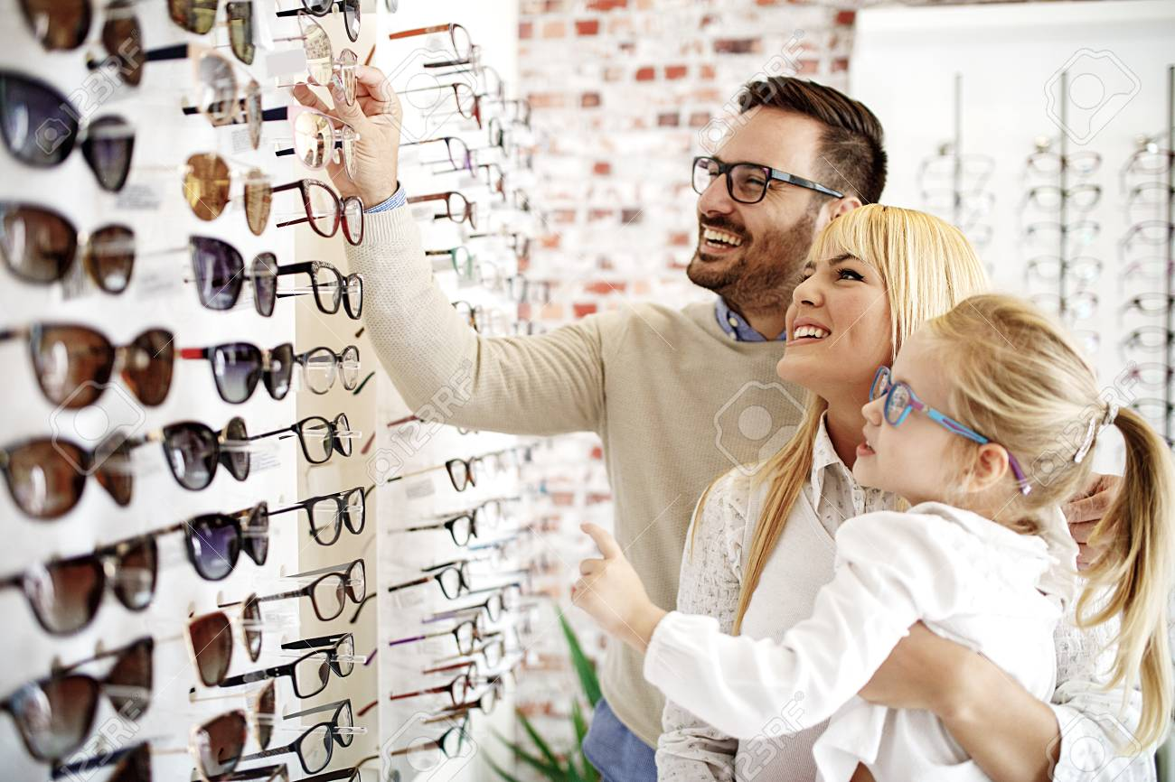 Four year little girl in optics store choosing glasses with her father. Ophtamologist helping. - 94418324