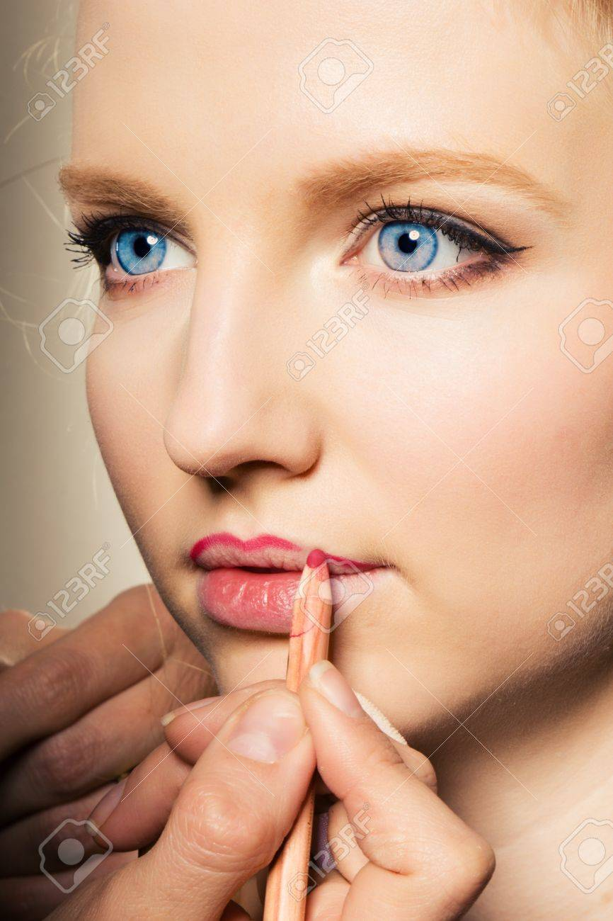 Portrait of a woman putting on lip liner. Stock Photo - 9943427