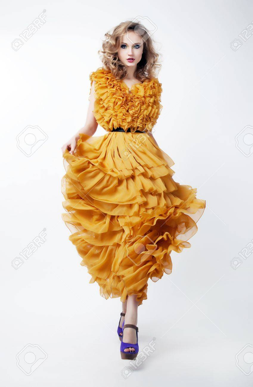 Beautiful female blonde fashion model in yellow dress isolated over white background Stock Photo - 12432973