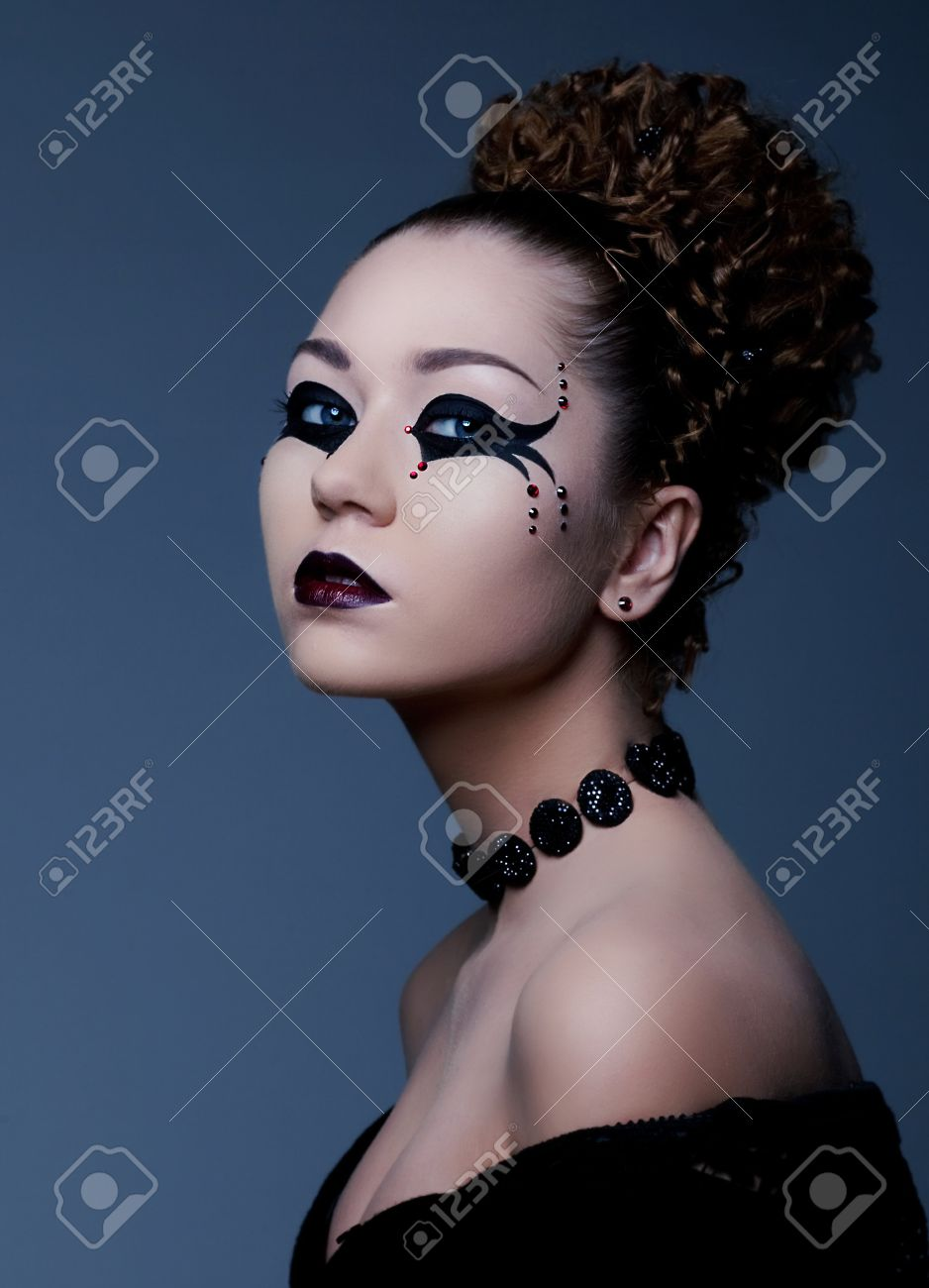 Fashion style portrait of a woman with dramatic theatrical makeup on her face Stock Photo -