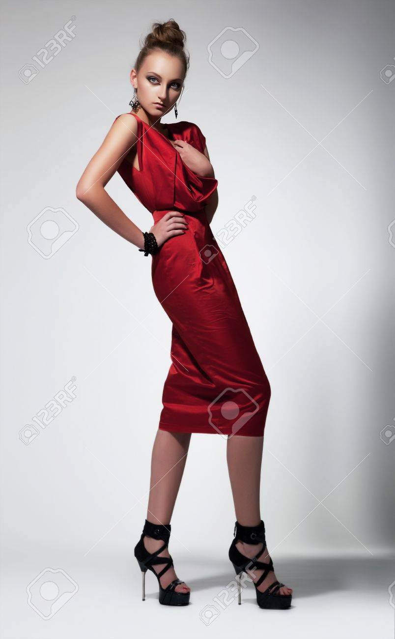Beautiful fashion woman in red dress posing in studio Stock Photo - 14293902
