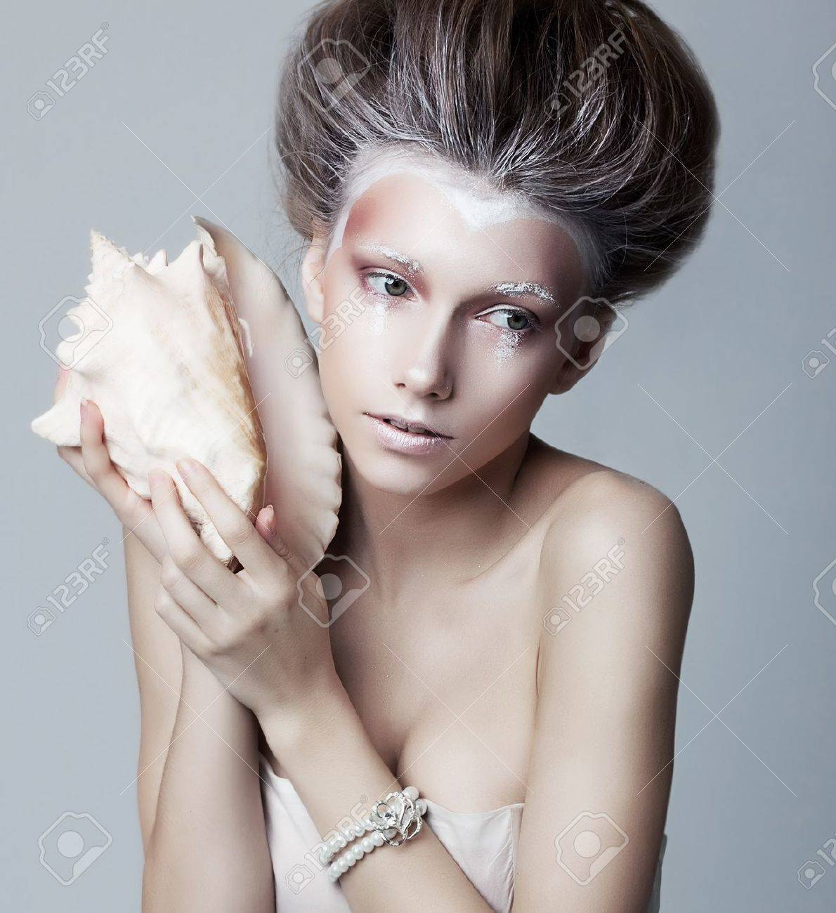 Beautiful young woman with seashell posing isolated  Series of photos Stock Photo - 14516711