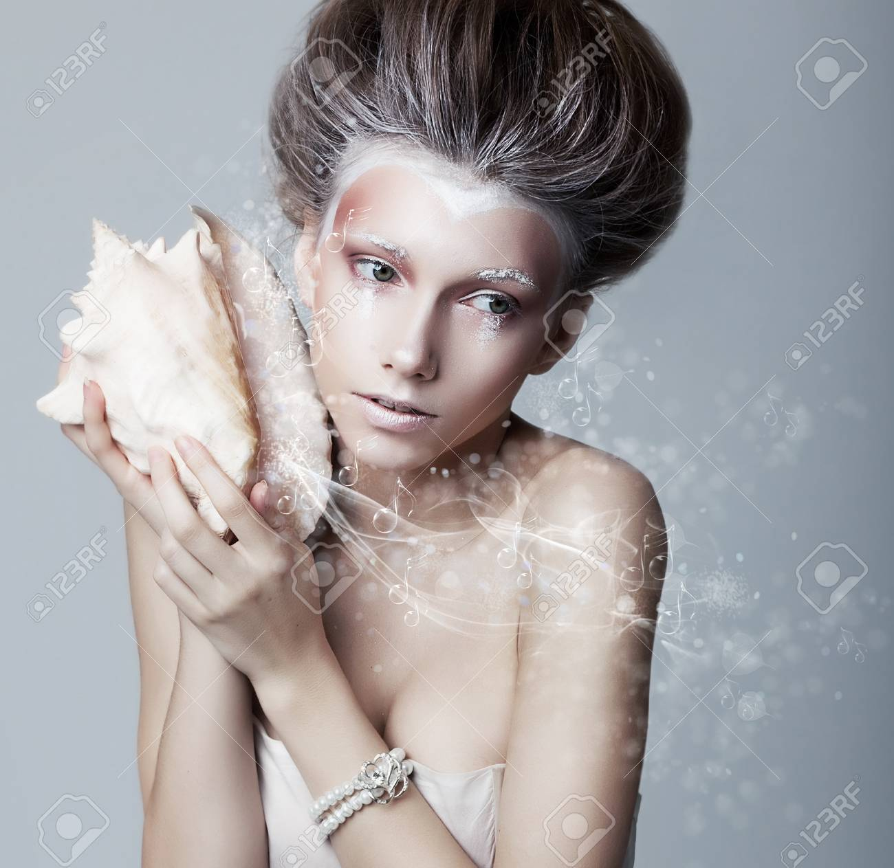 Beautiful girl with seashell in her hands  Flowing music  Lyrics Stock Photo - 14373112