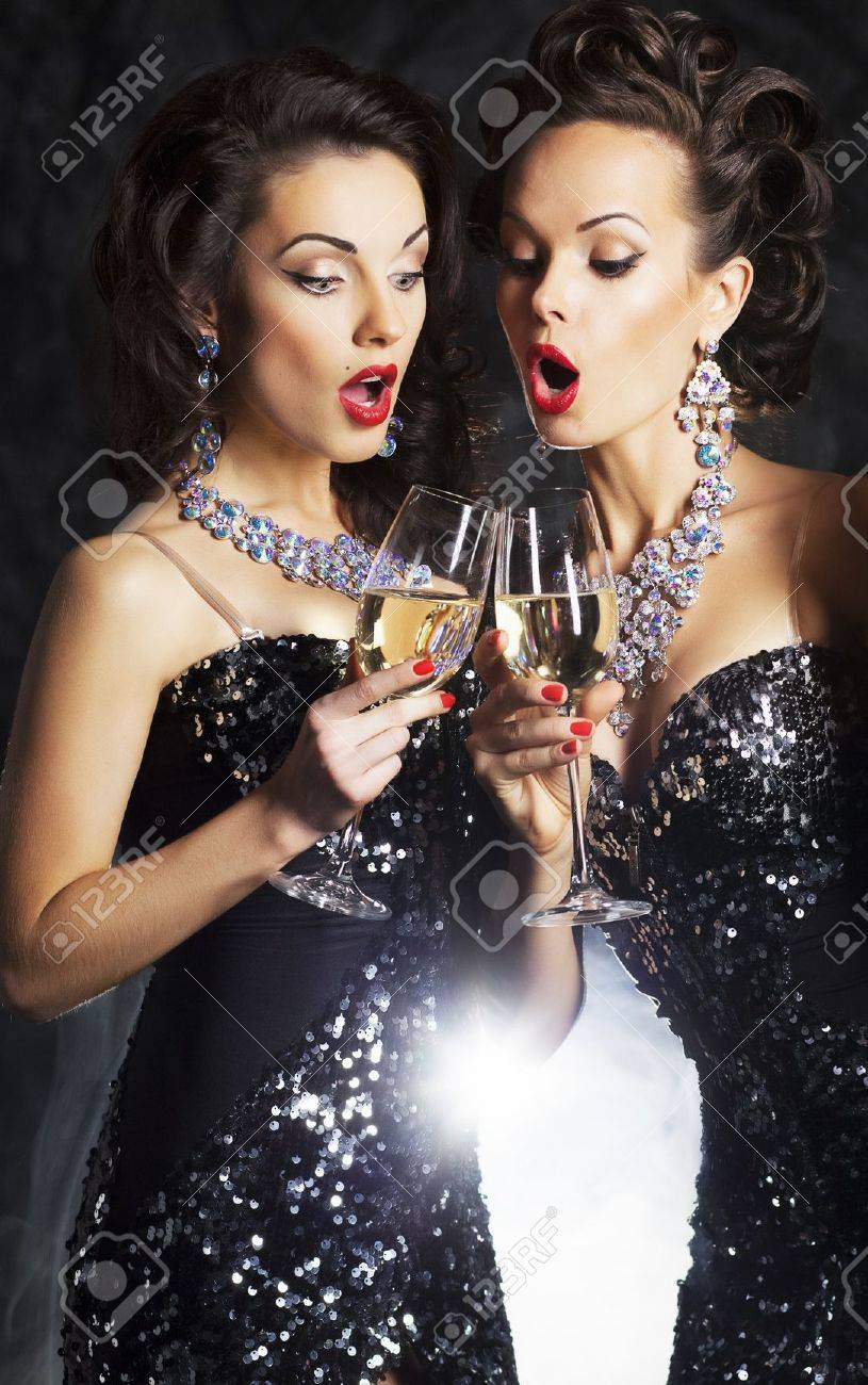 Couple of fashion women with flutes of sparkling champagne singing Christmas songs Stock Photo - 16237310